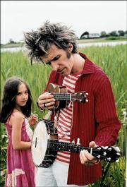 "Dan Zanes tunes his daughter Anna&squot;s ukulele. Zanes recently released his first video DVD collection of kid-friendly tunes, ""All Around the Kitchen!"""