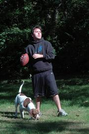 Trevor Ball, 20, Lawrence, a Johnson County Community College student, feels that if evolution is taught in schools intelligent design should also be taught. Ball was tossing around a football with a friend and his dog Sampson on Friday at his home in Lawrence.