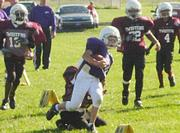 Bulldog Brandon Schmidt looks to gain a couple extra yards agains the Twisters defense Sunday at Youth Sports Inc.