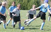 Silver Strikers Taylor Grob, center, works the ball through a pack of Blue Devil defenders as his teammate comes to help over the top Saturday at Youth Sports Inc. The Strikers edged the Devils in the defensively dominated contest, 1-0.