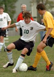 Free State's Greg Glatz, left, works the ball against Shawnee Mission West's Logan Murphy during Tuesday's match at Free State.