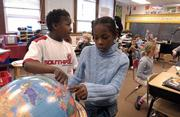 After a few moments of searching, Pinckney School fourth-graders Xavier Newman, left, and Khadijah Lane point to Iraq on a globe.