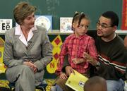 First lady Laura Bush, left, listens to Reynard Zweifel, right, as he talks about the importance of reading to his daughter, Amaya, center, during a group discussion at J.S. Chick Elementary School in Kansas City, Mo. The first lady met with fathers, their children and representatives from the National Center for Fathering as they discussed the roles that fathers have in their children's lives.