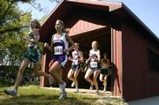 Runners race through a covered bridge during the Rim Rock Cross Country Classic on Sept. 17.