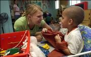 Kansas University fifth-year senior Jessica Giessen, Spring Hill, plays with Makyah Brockman, 4, at the Brookcreek Learning Center on the Lawrence High School campus. Brookcreek was cited for several violations and received a $2,000 fine.