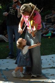 Grace O'Brien, 1, clings to her aunt, Ashley Willoughby, 19, of Quenemo, as Willoughby plays with the Ottawa Suzuki Strings ensemble Saturday at the 48th annual Maple Leaf Festival in Baldwin. The festival continues today.