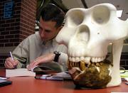 Novelist Eric Penz, of Seattle, signs one of his books for a buyer Saturday at the Texas Bigfoot Conference in Jefferson, Texas. The skull is a creation based on calculations from the jaw fossil, Penz said.