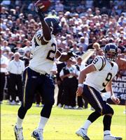San Diego's LaDainian Tomlinson throws for a second-quarter touchdown in the Chargers' 27-14 victory against the Raiders. Tomlinson tied an NFL record by scoring a touchdown in his 18th straight game, and then became the seventh player to run, catch and throw for a touchdown in the same game on Sunday in Oakland.
