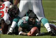 Miami's Ricky Williams, center, comes up without his helmet after taking a handoff during the first quarter against the Buccaneers. The Dolphins lost, 27-13, Sunday in Tampa, Fla.