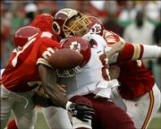 Washington Redskins quarterback Mark Brunell, center, fumbles the ball as he is hit by Kansas City's Jerome Woods, left, and Kawika Mitchell in the second quarter. Jared Allen recovered the fumble, helping the Chiefs beat the Redskins, 28-21, on Sunday at Arrowhead Stadium in Kansas City, Mo.