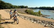 Marcus and Kathy Bassett, of Topeka, ride their bikes on the Kansas River levee bike trail  below the Bowersock Dam on Friday.