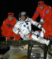 Chinese astronaut Nie Haisheng,  with the help of workers, gets out of the re-entry capsule of China's second manned spacecraft, Shenzhou 6, after landing today in Siziwang Banner, north China's Inner Mongolia Autonomous Region.