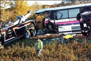 The wreckage of a bus that was transporting students from Chippewa Falls High School is readied to be removed Sunday near Osseo, Wis., after it collided with a semi truck. Five people on the bus were killed and 29 others were transported to the hospital.