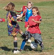 All-Stars forward Kennefi Conklin, left, challenges the Bobcats goalie for the ball Saturday at Youth Sports Inc.