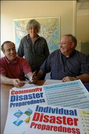 "Kansas University researchers have for years been working on ways to aid people with disabilities during major disasters like Hurricane Katrina. Researchers working on the project of ""Nobody Left Behind: Disaster Preparedness for Persons with Mobility Impairments"" are, from left, Michael Fox, associate professor of health policy and management at KU, Cat Rooney, project coordinator, and Glen White, director. In the foreground are posters that have resulted from some of the center's work and from content supplied by people with mobility limitations."