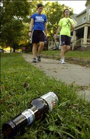 Kansas University freshmen Molly Herman, Topeka, left, and Maggie Frerker, Overland Park, walk past an empty beer bottle in the 1300 block of Tennessee Street Monday, October 18, 2005.