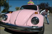 Nancy Thellman decorates a 1976 pink Volkswagen Beetle after parking it in the CEK Insurance lot, 1011 Westdale Road, to advertise the Stepping Out Against Breast Cancer Dance fundraiser.