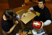 Rebecca Gant, left, and Sean Atchley pack up food for the poor at First United Methodist Church, 946 Vt. Members of the church hold food drives and assemble kits with heath goods, back-to-school items and baby items to fight poverty in Kansas.