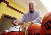 Texas Tech coach Bob Knight autographs a basketball at Big 12 Media Day.