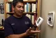 Randy Ortiz, president and owner of Advantage Heating & Air Conditioning in Lawrence, explains the installation of a programmable digital thermostat to a Lawrence homeowner. The programmable thermostat features touch-screen control that can help reduce the use of natural gas by lowering settings when a homeowner is away or asleep.