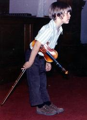 A young Brian Lewis takes a bow during a recital. Lewis, now 37 and a virtuoso violin player,  has performed at Lincoln Center and Carnegie Hall and released seven solo CDs. He'll honor his former teacher, Eleanor Allen, during a concert Sunday at the First Baptist Church in Lawrence.