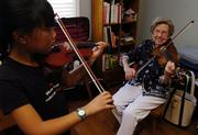 Eleanor Allen gives a violin lesson to Katherine Marshall-Kramer, 9, of Lawrence, Monday afternoon. Allen will be honored Sunday by former student Brian Lewis, now an accomplished violinist.