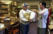 Paul Hunt, director of resources for the Ballard Community Center, hands a bag of non-perishable food items to Lawrence resident Marvin E. Copp on Thursday afternoon at the center's food pantry.