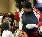 Aretha Franklin, the Queen of Soul, chats with 9-year-old Michael Barconey at a party she threw Friday in Southfield, Mich., for people displaced by Hurricane Katrina.