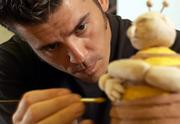 Lawrence artist Ben Ahlvers applies glaze to a work in his Bee Series before firing the piece in a kiln Wednesday afternoon at the Lawrence Arts Center. Ahlvers will display these and other works next weekend during the 11th annual Lawrence ArtWalk.