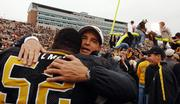 Missouri coach Gary Pinkel, right, hugs offensive lineman Tony Palmer as a goalpost is brought down. The Tigers beat Nebraska, 41-24, Saturday in Columbia, Mo.