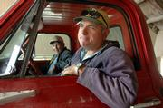 Larry Landis, right, watches soybeans pour from his truck bin as his father, Warren, sits alongside. They delivered soybeans to the North Lawrence Elevator with other farmers Wednesday morning, and already have worries about costs to produce next year's crops.