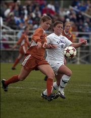 Texas' Priscilla Fite (12) battles for the ball against Kansas' Jessica Bush (7) during the first half of Sunday's game. Kansas defeated Texas, 2-1.