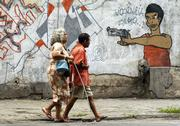 People pass graffiti Saturday in Rio De Janeiro, Brazil. Brazilians will vote today on whether they want to ban the sale of firearms. Brazil ranks second in deaths by guns with 21.72 per 100,000 people a year, behind only Venezuela with 34.3 gun deaths per 100,000.