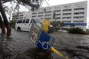 People try to cross a flooded street in the resort city of Cancun, Mexico, after the passing of Hurricane Wilma on Saturday. Wilma punished Mexico's Caribbean coastline for a second day, ripping away storefronts, peeling back roofs and forcing tourists and residents trapped in hotels and shelters to scramble to higher floors.