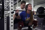 Cheryl Anderson attempts a power lift as Neal Anderson helps to spot her safety and progress. Anderson is 30 years old and weighs 97 pounds, and she has won some prestigious powerlifting medals.