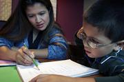 Anderson helps her 7-year-old son, Glen, study for a spelling test. Glen, a first-grader, will travel with his parents to Finland to watch his mom compete against other world-class lifters.