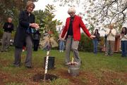 From Left, Kathy Habiger, Overland Park, Roger Hill's daughter, and Suzy Hill, Lawrence, Roger Hill's wife, applaud after planting a tree in his honor. The Saturday morning event celebrating the 15th anniversary of the Roger Hill Volunteer Center was on the front lawn at the United Way, 2518 Ridge Court.