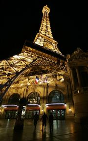 Tourists walk under the replica of the Eiffel Tower at the Paris Hotel and Casino on the Las Vegas Strip.