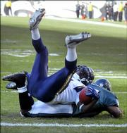 Philadelphia linebacker Keith Adams stops San Diego running back LaDanian Tomlinson, top, at the one-yard line in the fourth quarter. The Eagles held Tomlinson to a career-low seven rushing yards on 17 carries in their 20-17 victory over the Chargers on Sunday in Philadelphia.