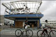 Bicyclists pass a store Sunday destroyed by Hurricane Wilma in Cancun, Mexico. Police in Cancun tried to protect both stores and foreign tourists from the looters, and the military set up checkpoints to seize stolen goods.