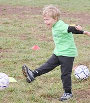 Joey Bassett smiles as he kicks the ball towards the net during warm-ups on Saturday at Youth Sports Inc.