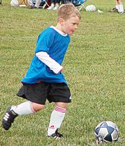 A Dragons player runs up to kick the ball Saturday at Youth Sports Inc.
