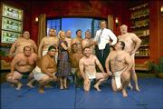 Talk show host Regis Philbin, in shirt and tie, gets a lift as fourteen sumo wrestlers descend on the Live with Regis and Kelly set. The athletes are in New York for a competition at Madison Square Garden. The group visited Philbin and co-host Kelly Ripa, center, to demonstrate the art of sumo.