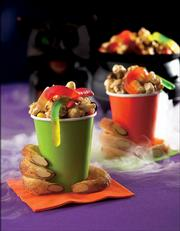 This photo provided by Woman's Day shows Monster Munch mix piled into colored cups grasped by Witchy Fingers - sweetly scary treats for Halloween, easily made at home.