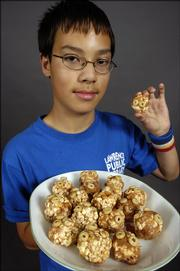 Eric Palmquist, a seventh-grader at Southwest Junior High School, shown with his Butterfinger Popcorn Balls.