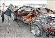 A television cameraman gets a close-up view of the damage to a 1994 Chevrolet Caprice that was being driven by Denver Broncos offensive lineman Dwayne Carswell when it was involved in a five-car accident. Carswell was in critical but stable condition after the accident Thursday in Aurora, Colo.