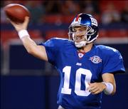 New York Giants quarterback Eli Manning passes against the Kansas City Chiefs in this Aug. 13, 2004 photo.