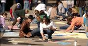 Kansas University students spread themselves out along Wescoe Beach as they participate in the Rock n' Chalk sidewalk chalking contest Thursday morning.