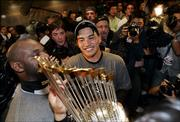 Chicago's Tadahito Iguchi, center, gazes at the World Series trophy after the White Sox swept the Astros. The Sox completed the sweep Wednesday night in Houston.