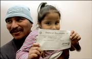 Litzy Ortiz, 4, holds a $2,688 check her father, Carlos Orellana, received Wednesday in Los Angeles after he learned of the unclaimed money. State controller Steve Westly is kicking off a campaign to find the owners of items from California's unclaimed property vault.